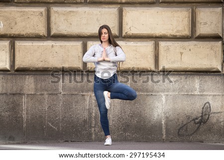 Sporty young woman on street working out in front of building wall, doing exercise for spine, standing in asana Vrikshasana (Vriksasana, Tree Pose), hands in Namaste, full length
