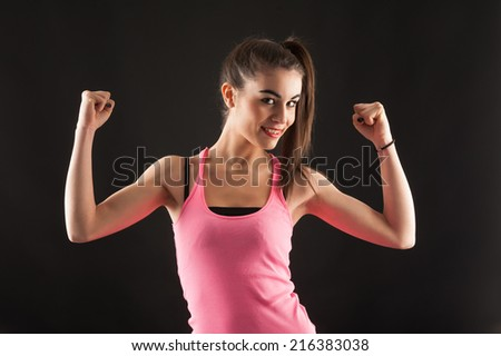 Sporty young woman portrait showing muscles isolated against black background.  - stock photo