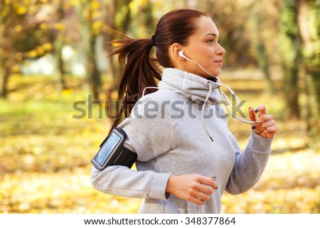 Sporty young woman running in the park and listening to music. Sport lifestyle. Motion blur. - stock photo