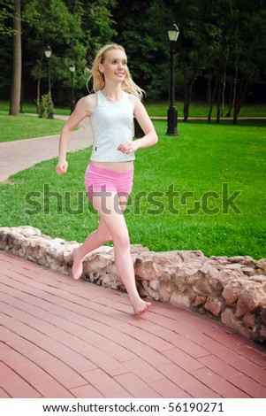 Sporty young woman running on the park