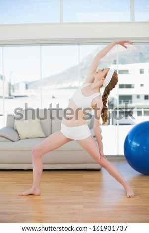 Sporty young woman stretching hand in fitness center