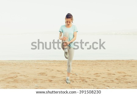 Sporty young woman stretching her legs and preparing to run on sand beach in summer, workout. Concept of healthy lifestyle