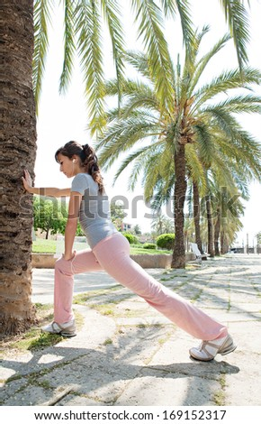 Sporty young woman training and stretching her legs in a park avenue with aligned palm trees during a sunny summer day while listening to music on her headphones, outdoors.