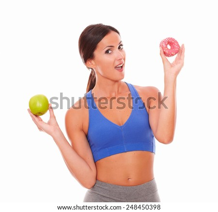 Sporty young woman wanting to eat sugary cake against white background