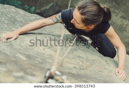 Sporty young woman wearing in safety equipment with rope climbing on stone rock in summer outdoor, top view