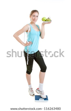 Sporty young woman with scales and apple on a white background. Concept of healthy lifestyle - stock photo