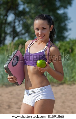 Sporty young woman with scales and green apple. Outdoors. Concept of healthy lifestyle. - stock photo