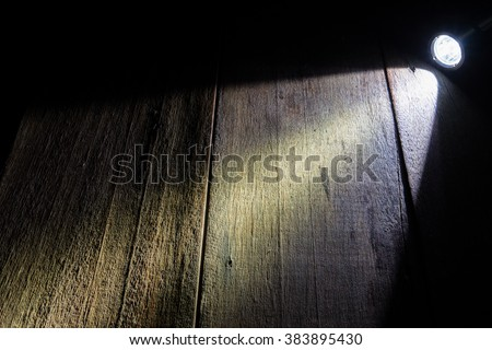 spot flashlight beam on wood bckground - stock photo