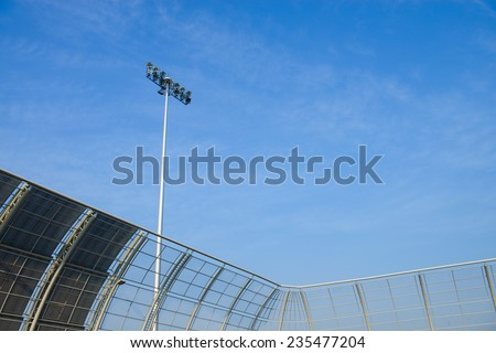 Spot-light tower in a stadium with blue sky - stock photo