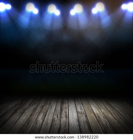 spot lighting over dark background and wood floor - stock photo