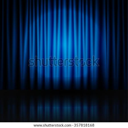 Spotlight on blue stage curtain - stock photo