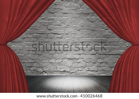 Spotlight on stage with red curtains, on old brick wall background. - stock photo