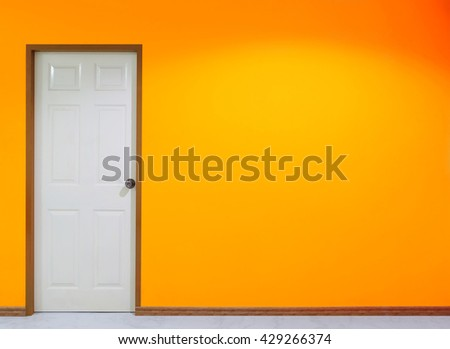 Spotlight on the orange wall and close white door for background. Have copy space for fill text or add object.