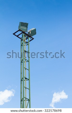 Spotlight tower against the blue sky background - stock photo