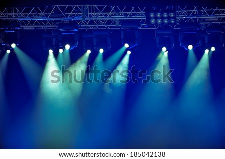 Spotlights and illumination equipment with fog on stage background - stock photo