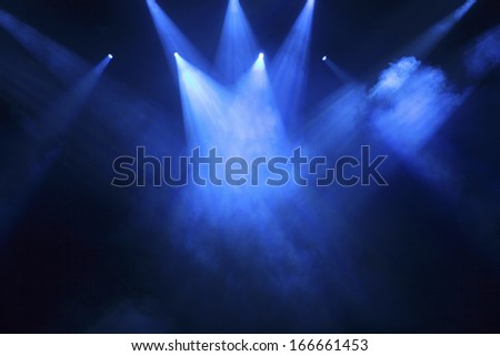 spotlights that illuminate the stage at a concert with fog