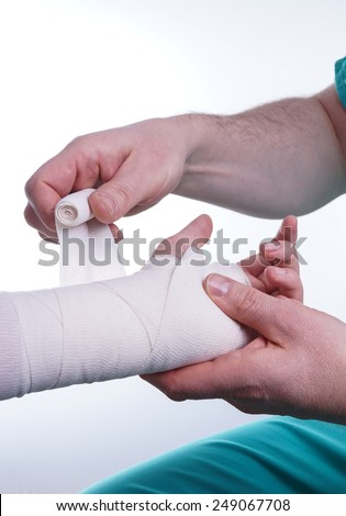 Sprained hand, Doctor helping with the Bandage - stock photo