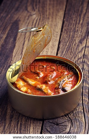 Sprat in tomato sauce on vintage wooden background - stock photo
