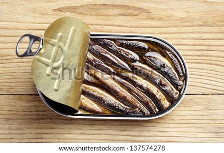 Sprat with oil in an open tin can on a wooden table - stock photo