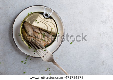 Sprats or sardines in can on stone background, selective focus