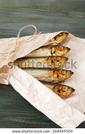 sprats packed in a white paper on the table - stock photo