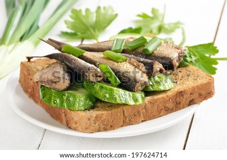 Sprats sandwich on white plate on wooden table - stock photo