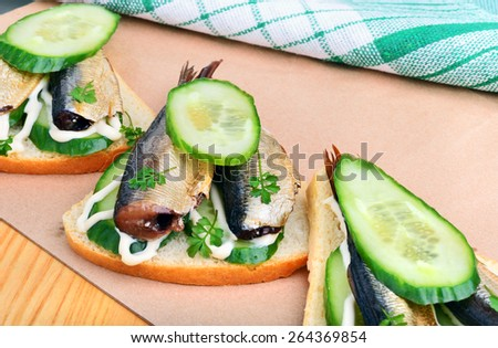 Sprats sandwiches, appetizer on paper background  - stock photo