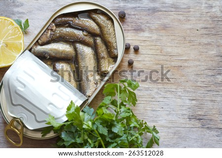 Sprats with oil in tin can on wooden board - stock photo