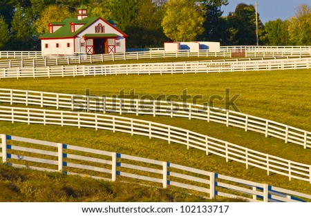 Sprawling acres of fenced in green pastures surround a horse farm ranch in Kentucky, USA