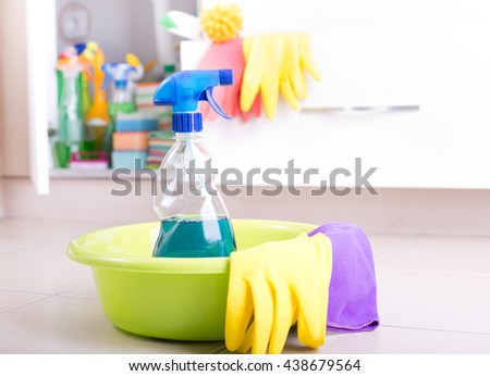 Spray bottle and cleaning tools in washbasin on the floor with supplies stored in kitchen cabinet in background