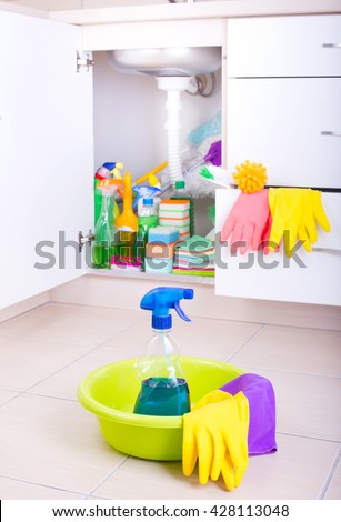 Spray bottle and cleaning tools in washbasin on tiled floor. Supplies and equipment stored in kitchen cabinet in background