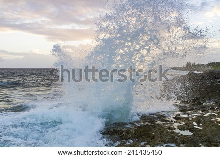 Spray from the famous Blow Holes on the south coast of Grand Cayman is backlit from the setting sun. - stock photo