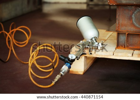 Spray gun on wooden stand, closeup