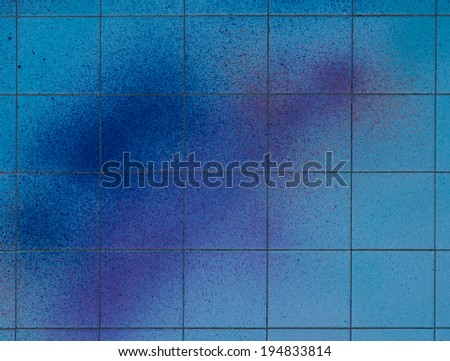 Spray of color on a blue square tile wall.