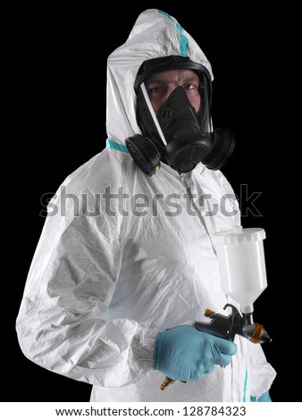Spray painter wearing white coverall, respirator and spray gun shot over black background