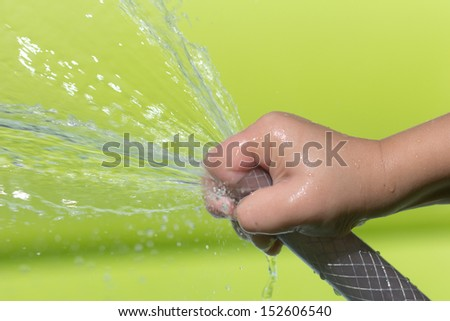 spray water from a hose child's hand - stock photo