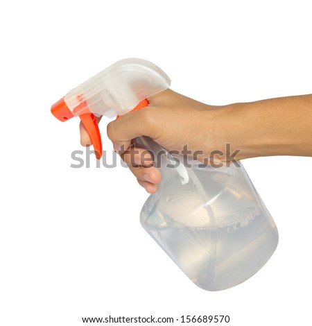 Spraying a cloth with laundry detergent in spray bottle. - stock photo