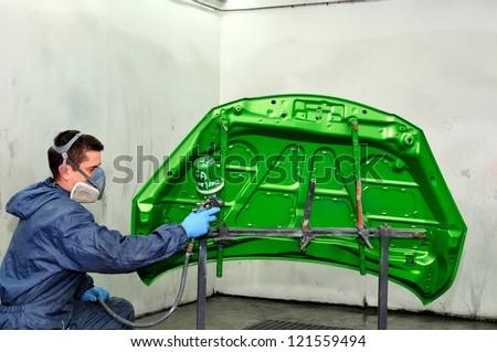 Spraying a green bonnet. - stock photo