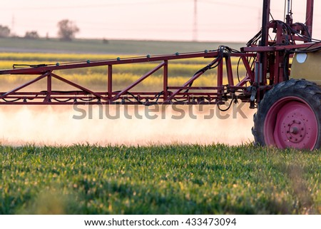Spraying machine working on the green field - stock photo