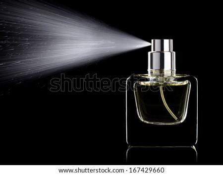 Spraying perfume bottle glass on a black background isolated - stock photo