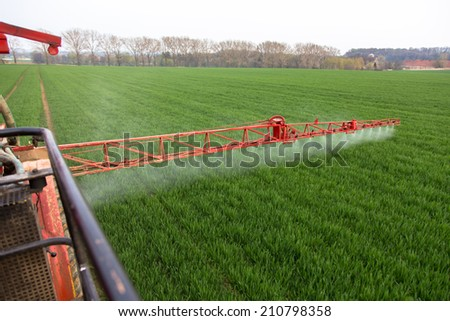 Spraying the herbicides on the green field - stock photo