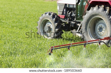 Spraying wheat crops field with tractor and sprayer - stock photo