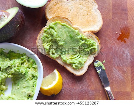 Spreading mashed avocado on toast slices