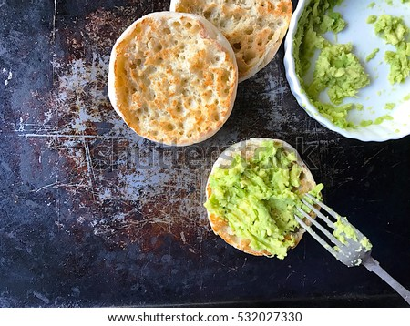Spreading mashed avocados on toasted English muffins