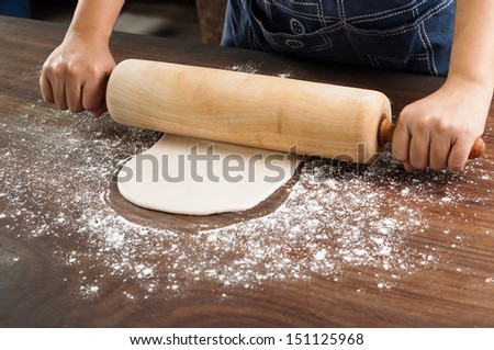 Spreading out pie dough with wooden rolling pin. - stock photo