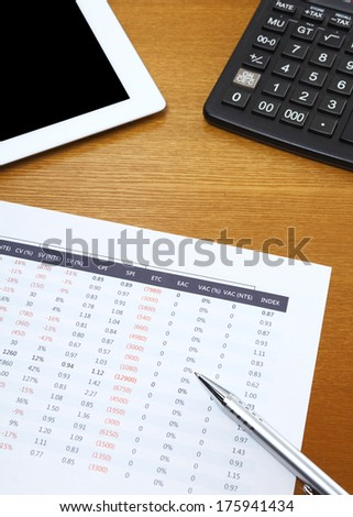 Spreadsheet with tablet and calculator - stock photo