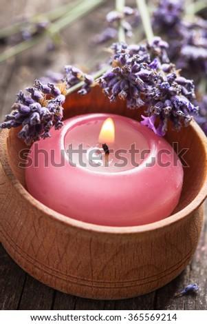Sprig of fragrant lavender alongside a burning aromatic candle - stock photo