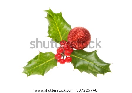Sprig of Holly with a red glitter Christmas bauble isolated against white - stock photo