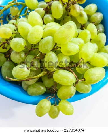 sprigs of green grapes in a colander, raw fruits - stock photo