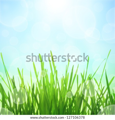 Spring abstract nature background with sun effect and bokeh. Green grass with blue sky - stock photo